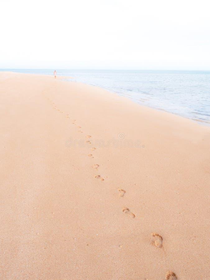 Voetafdrukken op een tropisch strand die naar horizon met een vrouw ver weg langzaam verdwijnen royalty-vrije stock foto's