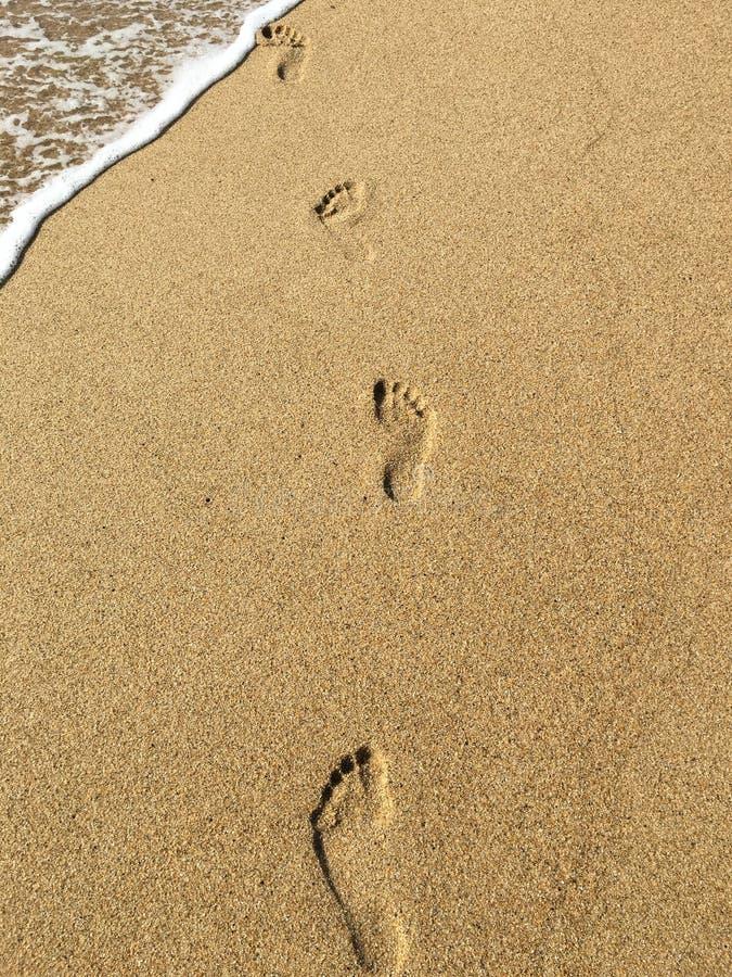 Voetafdrukken op het gouden zand stock afbeelding