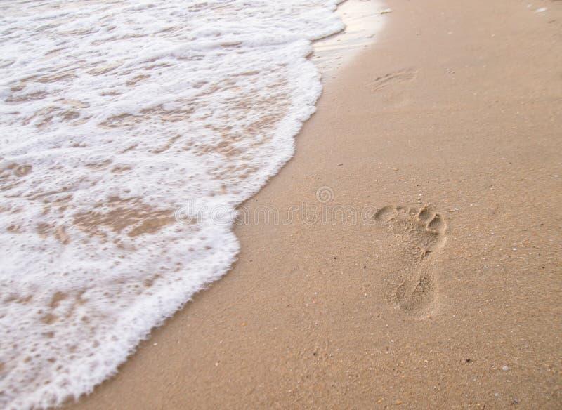 Voetafdrukken op het strand met overzeese golven royalty-vrije stock fotografie