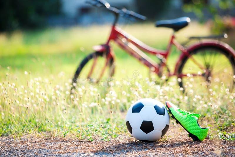 Voetbal en voetbalschoenen met onscherp van rode fiets en groen gras royalty-vrije stock fotografie