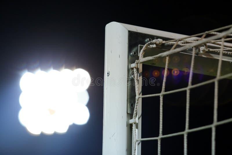 Voetbal of voetbal netto achtergrond, mening van achter het doel met vaag stadion en gebiedshoogte stock fotografie