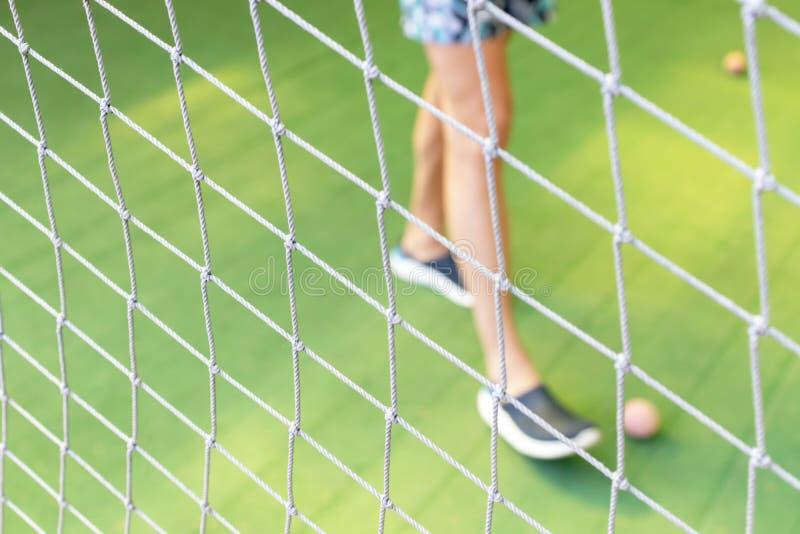 Voetbal netto dichte omhooggaand op het vage groene gebied van de grasvoetbal en mannelijke voeten die een kleine balachtergrond  royalty-vrije stock foto
