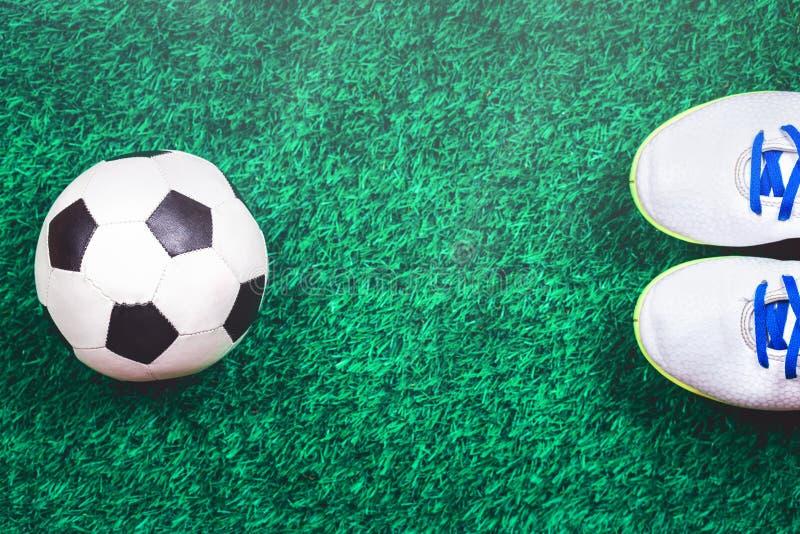 Voetbalbal en cleats tegen groen kunstmatig gras stock fotografie