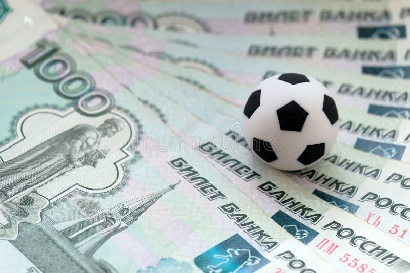 Voetbalbal op de verscheidene Russische roebels Het concept kosten en opbrengsten voor het kampioenschap, de ventilators, de spel stock foto