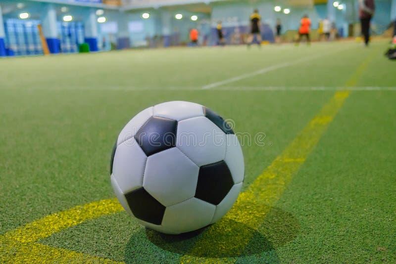 Voetbalbal op een lijn van de hoekschop op een kunstmatig groen gras stock foto