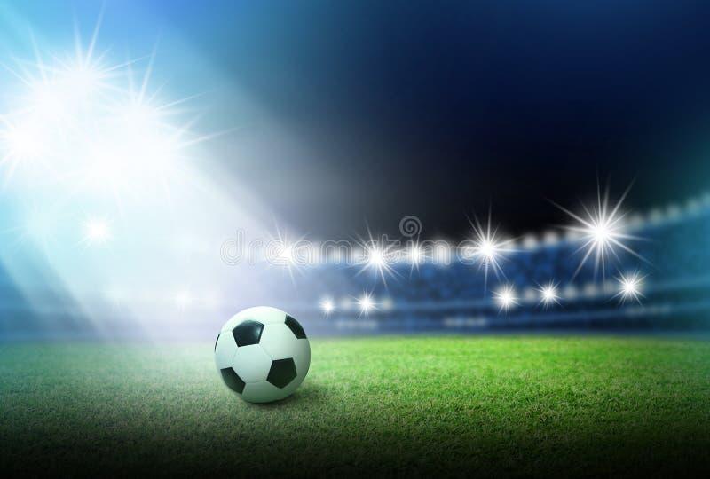 Voetbalbal op groen gras in stadion met schijnwerper stock afbeelding