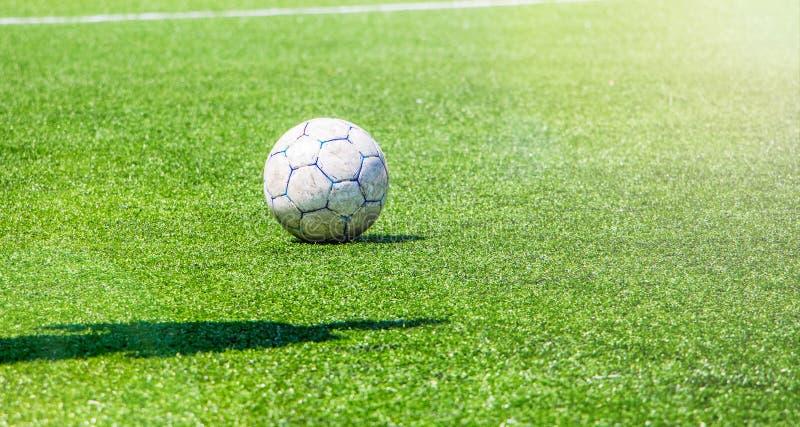 Voetbalbal op het groene gras van het stadion en de schaduw van een voetbalster in zonnige weather_ royalty-vrije stock fotografie
