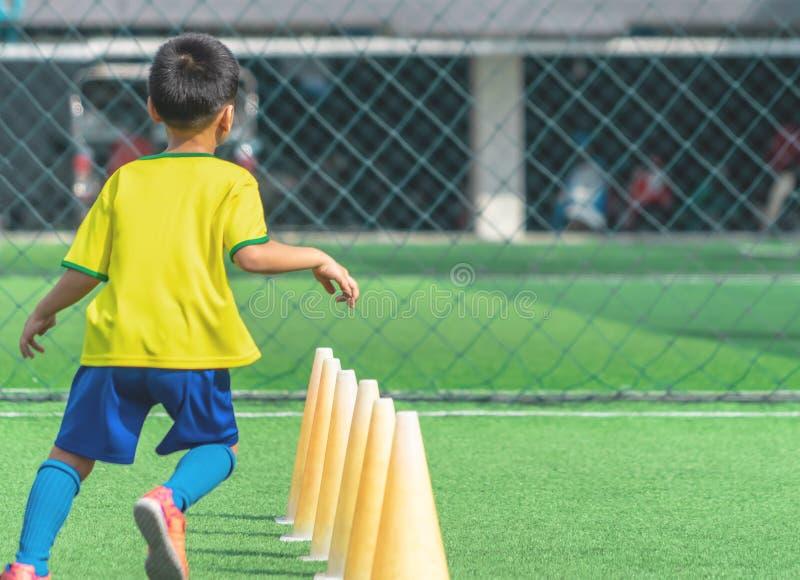 Voetbaljongen opleiding alleen met kegel op opleidingsgrond royalty-vrije stock afbeelding
