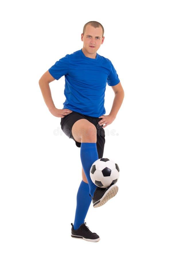 Voetballer in blauwe eenvormige makende geïsoleerde truc met bal royalty-vrije stock foto