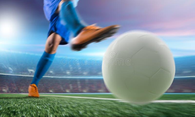 Voetballer in de bal van de actieschop bij stadion stock foto's