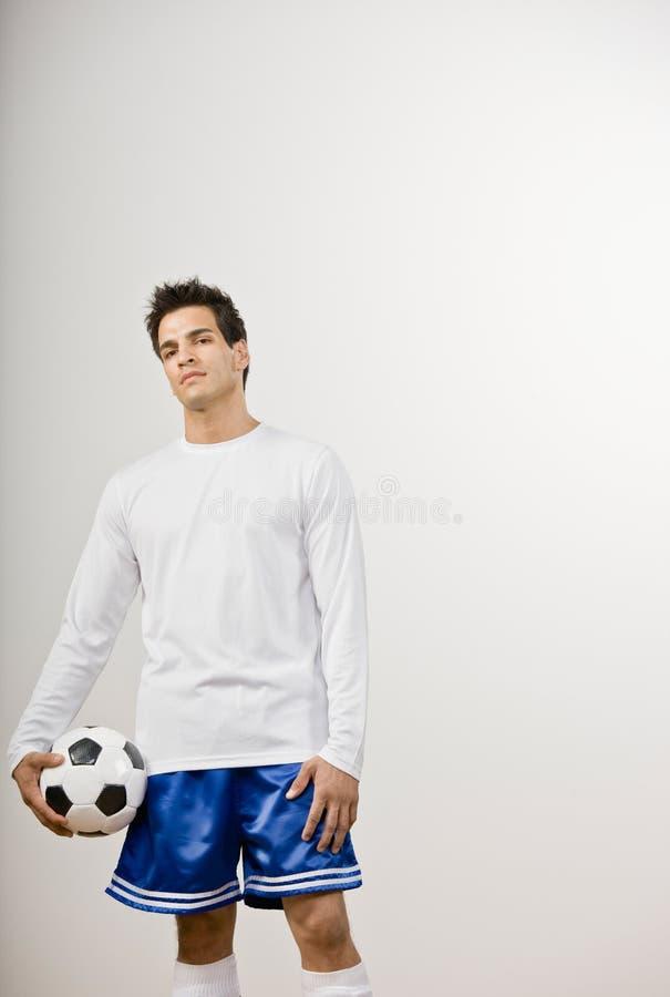 Voetballer in de eenvormige bal van het holdingsvoetbal royalty-vrije stock foto