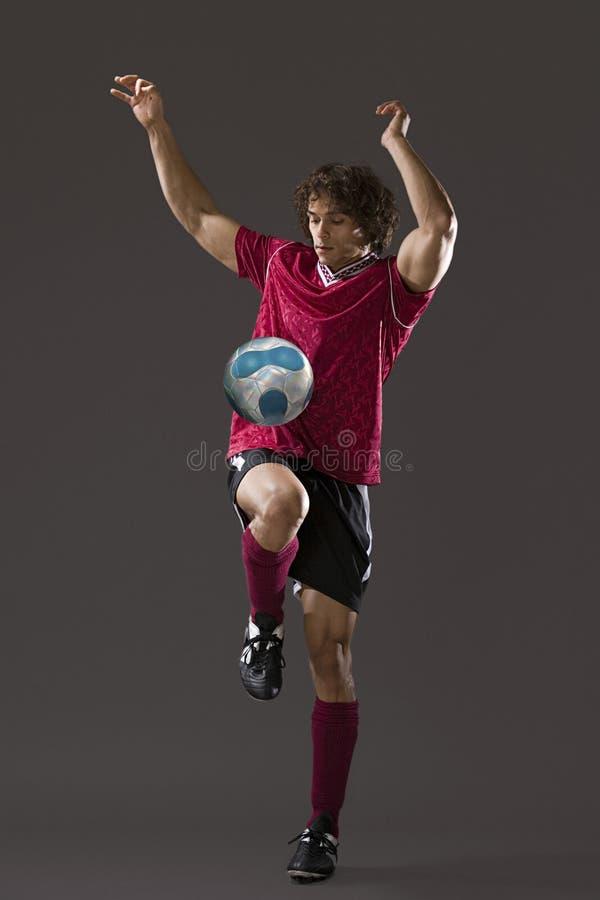 Voetballer die keepy uppy spelen stock afbeelding