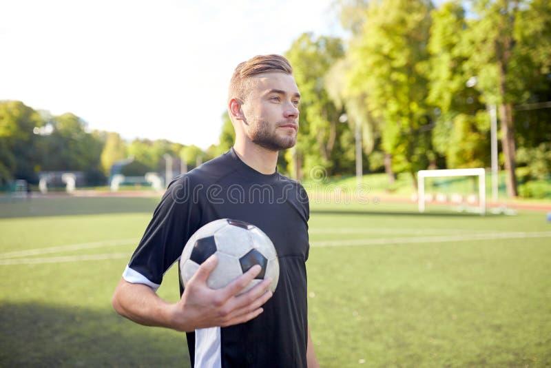Voetballer met bal op voetbalgebied royalty-vrije stock fotografie