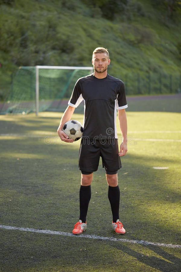 Voetballer met bal op voetbalgebied stock afbeeldingen