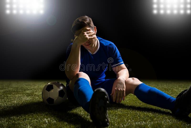 Voetballer teleurgestelde zitting op het grasgebied stock afbeeldingen