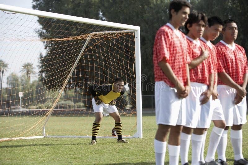 Voetballers die op een rij bevinden zich voorbereidingen treffend voor Vrije Schop stock fotografie