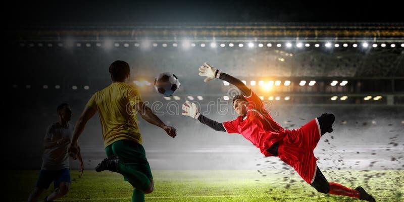 Voetballers op stadion in actie Gemengde media stock afbeelding