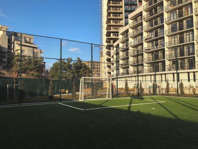 Voetbalpoorten aan de sportengrond in de stadsyard op de achtergrond van een nieuwe woningbouw stock foto