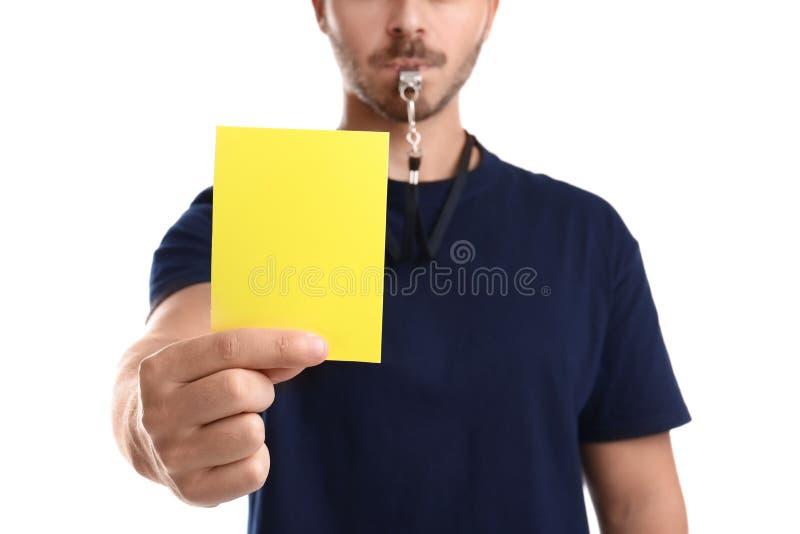 Voetbalscheidsrechter die gele kaart op witte achtergrond houden stock foto's