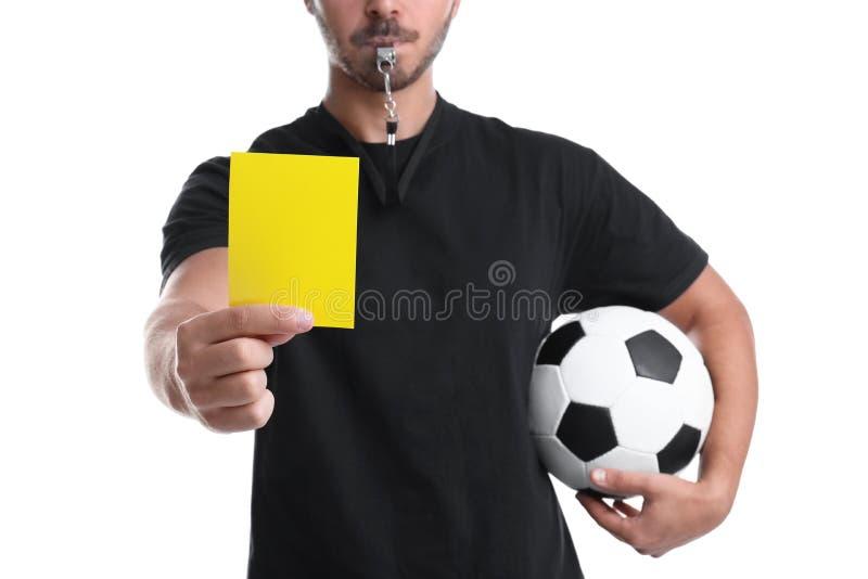 Voetbalscheidsrechter die met bal gele kaart houden stock fotografie