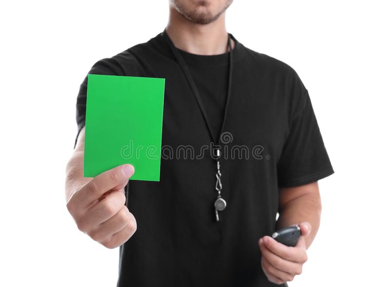 Voetbalscheidsrechter met chronometer en fluitje die groene kaart op witte achtergrond houden stock afbeelding