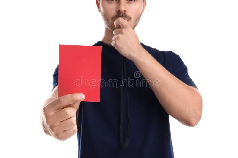 Voetbalscheidsrechter met fluitje die rode kaart op witte achtergrond houden stock foto's