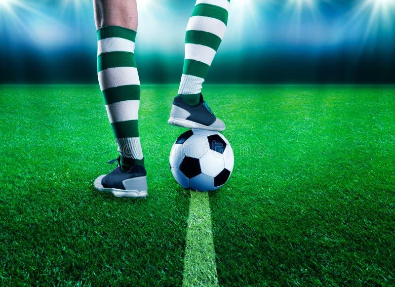 Voetbalster op de voetbalgrond stock foto's