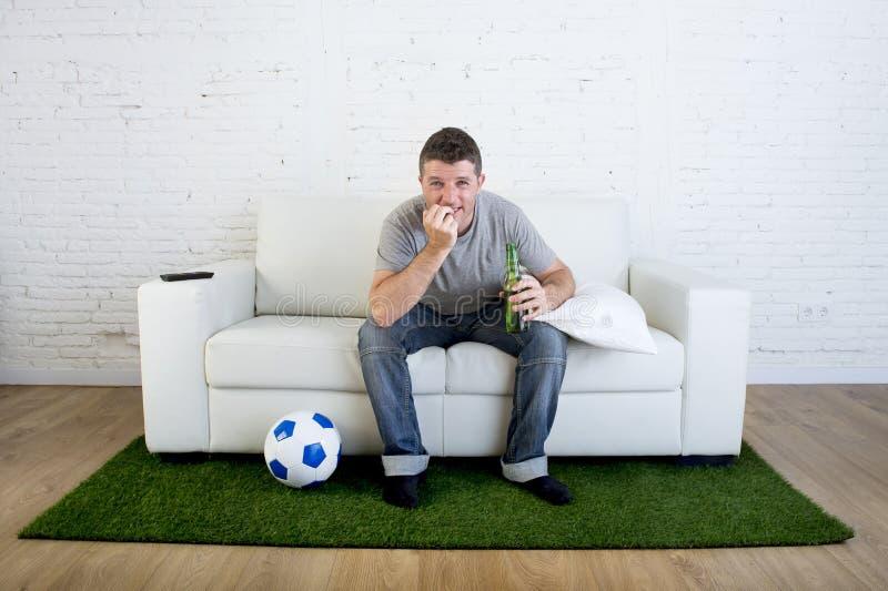 Voetbalventilator die TV-op gelijke op bank met tapijt i letten van de grashoogte royalty-vrije stock foto's