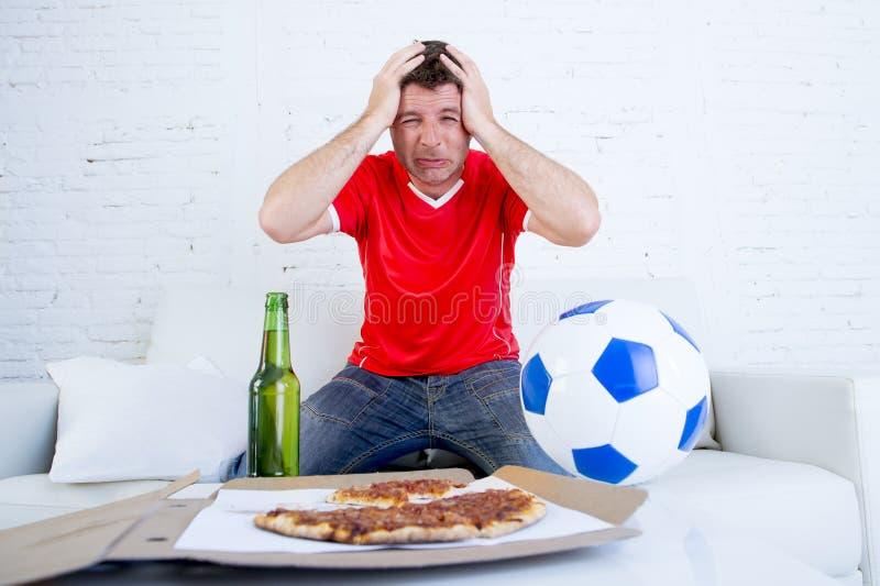 Voetbalventilator het letten op voetbalspel op droevige teleurgesteld van TV en wanhopig royalty-vrije stock fotografie