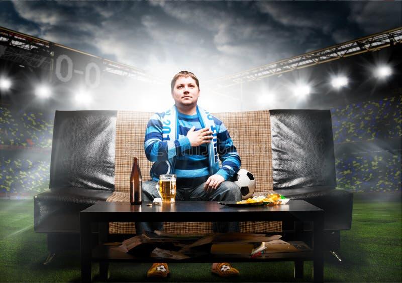 Voetbalventilator op bank royalty-vrije stock afbeelding
