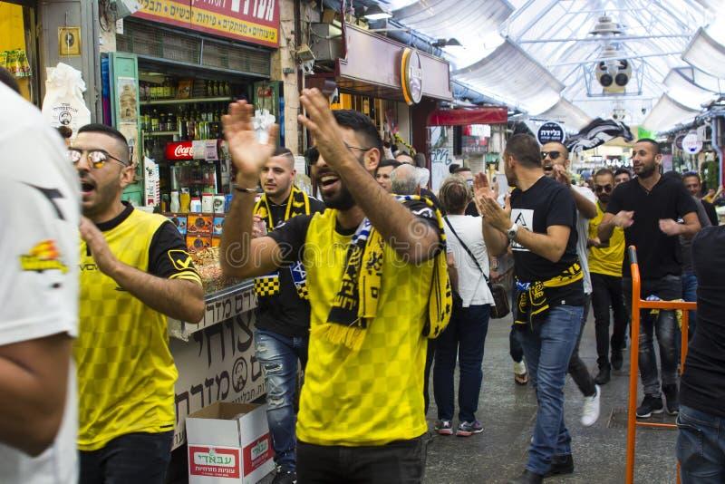 Voetbalverdedigers in Beitar Jerusalemstrook maart onderaan de wandelgalerij van de markthal van Mahane Yehuda in Jeruzalem Israë stock afbeeldingen