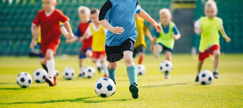 Voetbalvoetbal opleiding voor jonge geitjes Jonge jongens die de Kinderenvoetbal van voetbalvaardigheden opleiding verbeteren royalty-vrije stock afbeelding