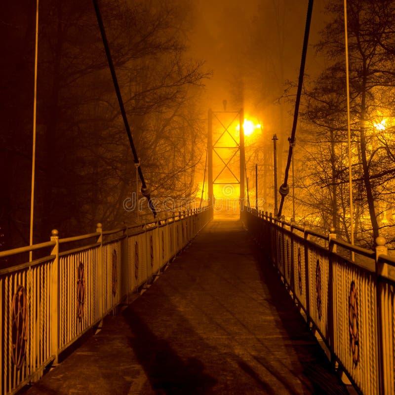 Voetbrug in dichte mist bij nacht stock foto's