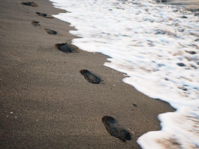 Voetdrukken op een zwart zandstrand met schuine stand-verschuiving onduidelijk beeld Branding op achtergrond Concept voor eenzaam stock fotografie