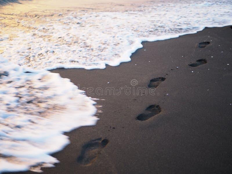 Voetdrukken op een zwart zandstrand met schuine stand-verschuiving onduidelijk beeld Branding op achtergrond Concept voor eenzaam stock foto's