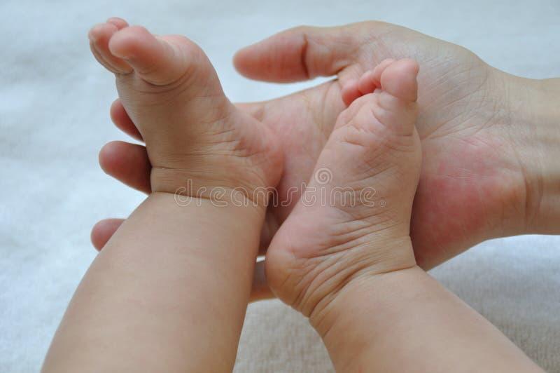 Voeten en moederhanden 2190 van de baby