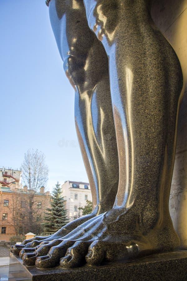 Voeten graniet atlantes in de kluis van St. Petersburg in R stock fotografie