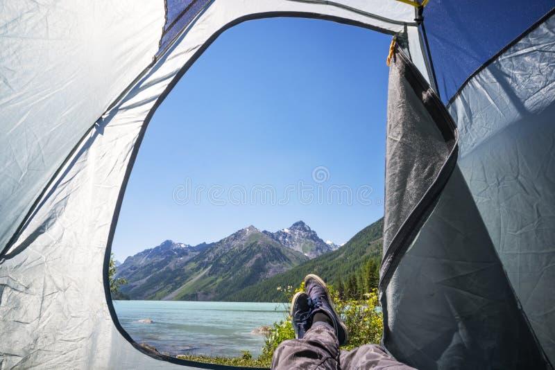 Voeten klimmermens het ontspannende letten op van tent openlucht kamperen Het concept van de reislevensstijl op de kust van een s stock afbeelding