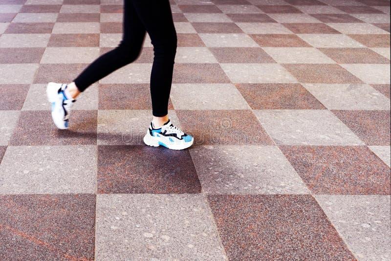 Voeten meisjes in tennisschoenen, die op een steentegel lopen royalty-vrije stock afbeelding