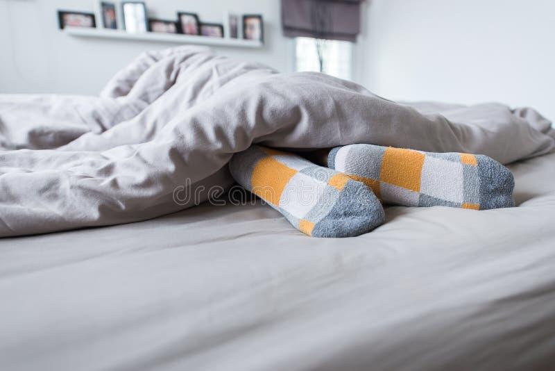 Voeten met sokken, Voet op het bed onder deken stock foto's