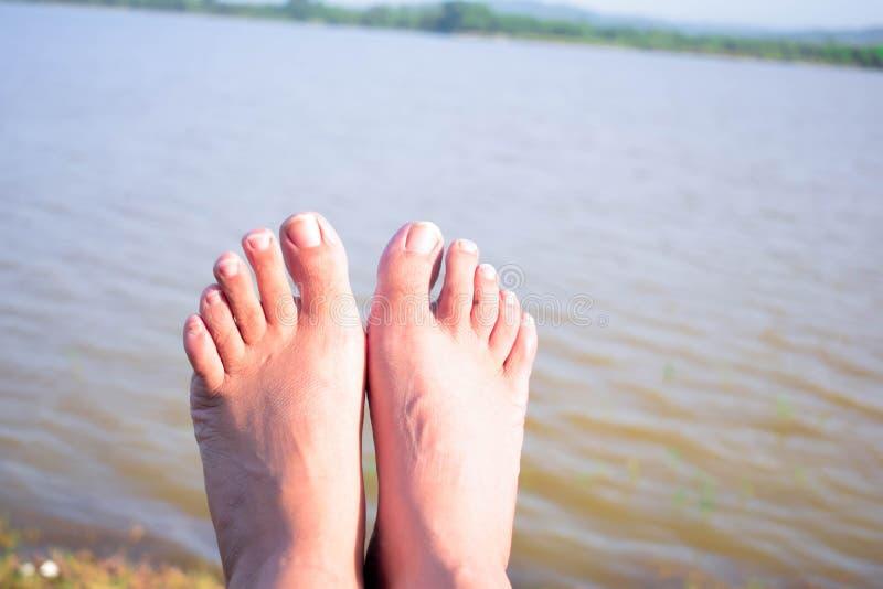VOETEN NAAR WATER IN DORPSrivier stock foto