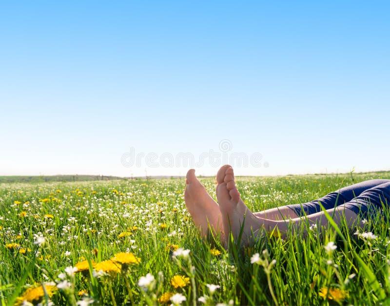 Voeten op de lentegras en bloemen stock afbeeldingen