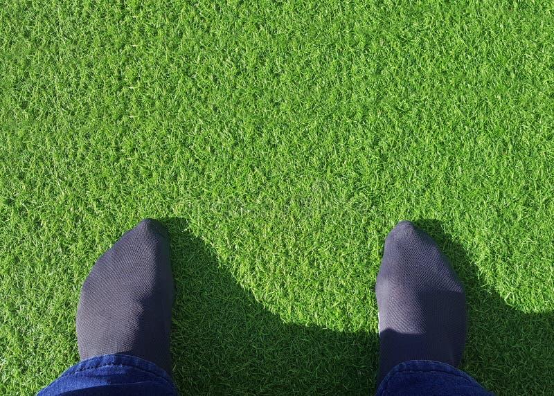 Voeten op kunstmatig gras stock foto