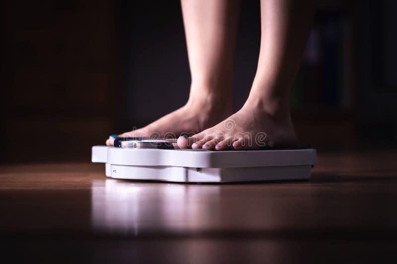 Voeten op Schaal Gewichtsverlies en dieetconcept Vrouw die weegt Geschiktheidsdame het op dieet zijn Weightloss en voedingsleer royalty-vrije stock foto