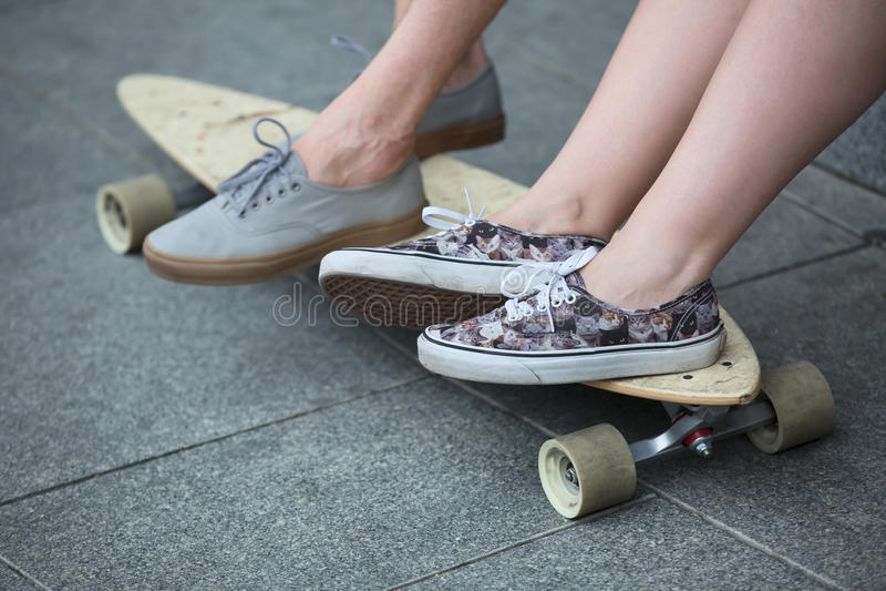Voeten paar van tieners in tennisschoenen op longboard stock afbeeldingen