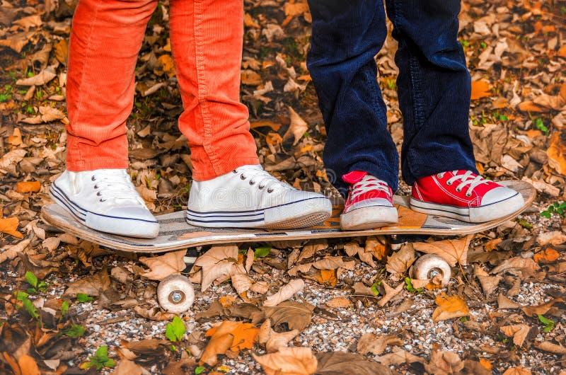 Voeten in tennisschoenen op een skateboard twee de kinderenherfst stock foto