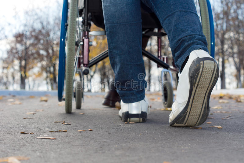 Voeten van een persoon die een rolstoel duwen stock foto's