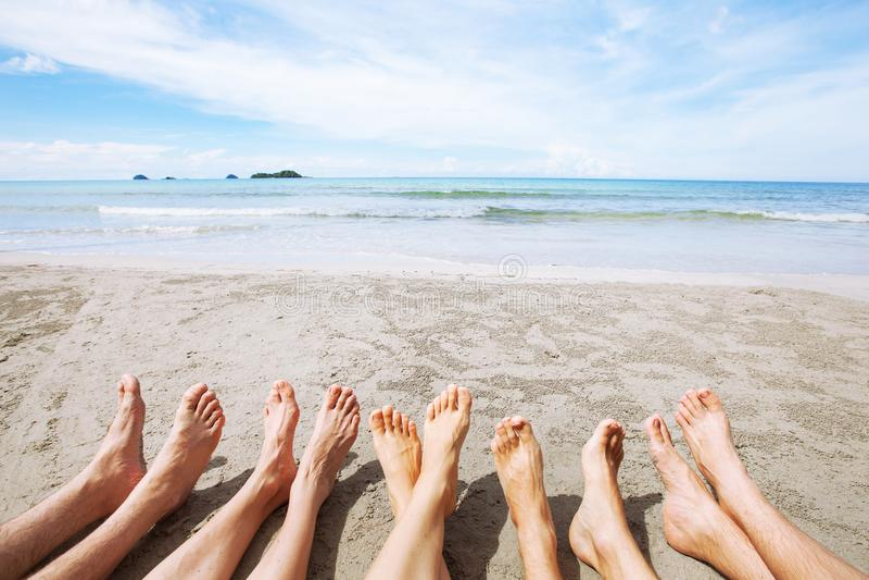 Voeten van familie of groep vrienden op het strand, vele mensen die samen zitten royalty-vrije stock fotografie