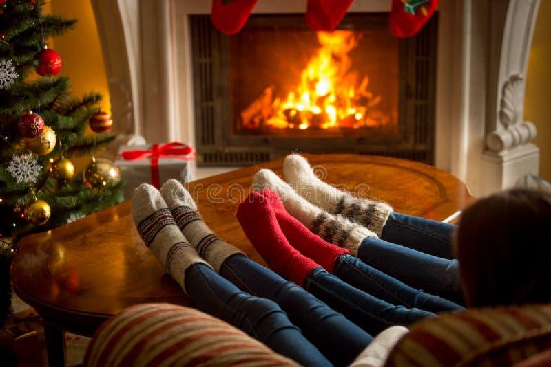 Voeten van familie in wollen sokken die bij het branden van open haard bij l verwarmen royalty-vrije stock afbeeldingen