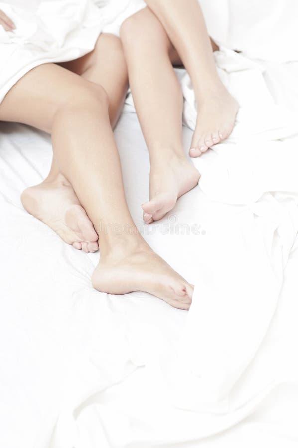 Voeten vrouwen in bed stock fotografie